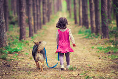 Little girl walking with dog. In the forest back to camera
