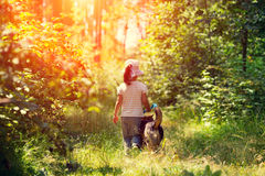 Little girl walking with dog in the forest Stock Photo