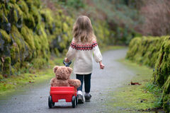 Little Girl Walking Down The Path Pulling Red Wagon With Teddy Bear Royalty Free Stock Image