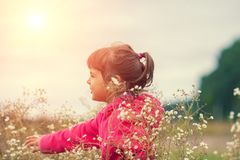 Little girl walking on the flower meadow royalty free stock image
