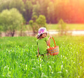 Little girl walking on the green field Stock Images