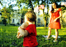 Little girl walking on green grass with mother outside, having fun, lifestyle people concept Stock Photo