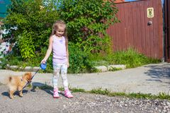 Little girl walking with her ??dog on a leash Stock Photo