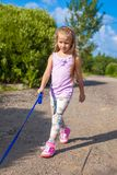 Little girl walking with her ??dog on a leash Stock Image
