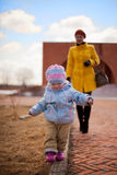 Little girl walking with her mother Stock Photos