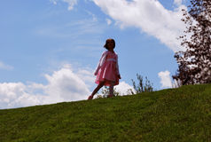 A little girl walking on the hill Stock Photos