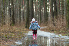 Little girl walking on icy puddle Royalty Free Stock Images