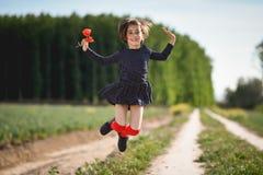 Little girl walking in nature field wearing beautiful dress Stock Photo