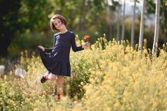 Little girl walking in nature field wearing beautiful dress Royalty Free Stock Photo