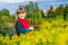 Little girl walking outdoors in the summer meadow with yellow flowers Royalty Free Stock Image