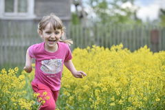 Little girl walking outdoors in the summer meadow with yellow flowers Royalty Free Stock Photo