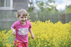 Little girl walking outdoors in the summer meadow with yellow flowers Stock Photos