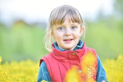 Little girl walking outdoors in the summer meadow with yellow flowers Stock Photography
