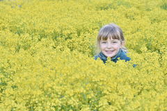 Little girl walking outdoors in the summer meadow with yellow flowers Royalty Free Stock Images