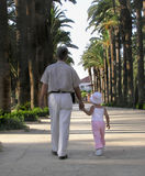 Little girl walking in a park with her grandfather. Little girl walking in a public park with her grandfather Stock Images