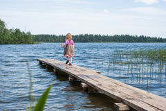 Little girl walking on the pier at the lake. Valdai royalty free stock photo