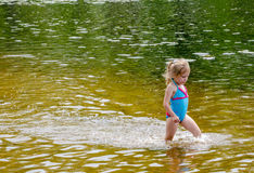Little girl walking in a pond Stock Images