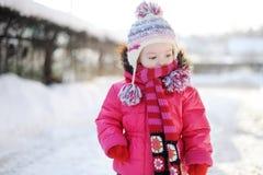 Little girl walking in purple wintercoat Royalty Free Stock Photo