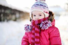 Little girl walking in a purple wintercoat Stock Photography
