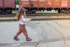 Little girl walking on railway station with the train on background.  Stock Photography