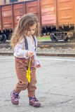 Little girl walking on railway station with the train on background.  Stock Photos