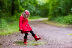 Little girl walking in the rain Stock Images