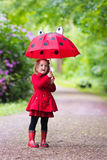 Little girl walking in the rain Royalty Free Stock Photos