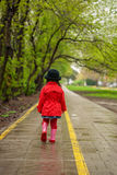Little girl walking on a rainy autumn day Stock Photography