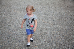 Little girl walking in the rays of setting sun in the park on background of gravel Royalty Free Stock Images