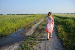 Little girl walking on the road stock images