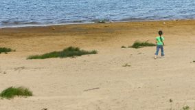 Little girl walking on a sandy shore of the lake Stock Images