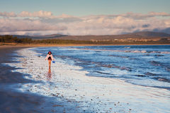 Little girl walking on shore at sunset Stock Photography