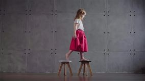 Little girl walking on small chairs. Side view of an adorable little girl wearing a pink skirt walking on small wooden chairs in a gray wall room. Locked down stock footage