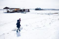 Little girl walking in snow in warm cloths stock images