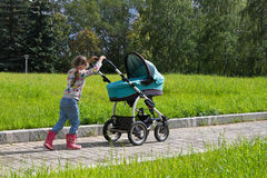 Little girl walking with stroller alone Royalty Free Stock Images