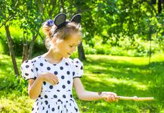 Little girl in summer park with small butterfly sitting on her hand. Little girl walking in summer park with small butterfly sitting on her hand royalty free stock photos