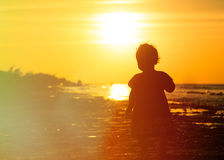 Little girl walking at sunset beach Stock Image