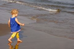 Little girl walking towards the seashore Royalty Free Stock Images