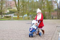 Little girl walking with toy stroller in the park Stock Photo