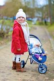 Little girl walking with toy stroller in the park Royalty Free Stock Photography