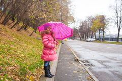 Little girl walking under an umbrella in the Stock Photography