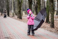 Little girl walking under umbrella in a park royalty free stock photo