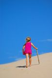 Little girl walking up sand dune Stock Photography