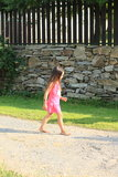 Little girl walking by a wall with fence. Little barefoot girl in pink dress walking on asphalt street by a stoned wall with wooden fence Royalty Free Stock Images
