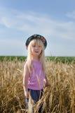Little girl walking in a wheat field Stock Photo