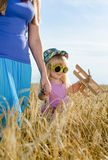 Little girl walking in a wheat field with mother Royalty Free Stock Photo