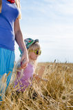 Little girl walking in a wheat field with mother Royalty Free Stock Photos