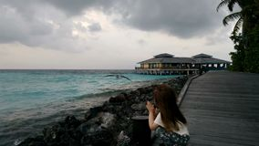 A little girl walking on a wooden pier and looking at the bird. Beautiful sea background. Maldives. 4k stock footage