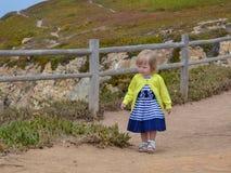 Little girl walks along the fence at Cape Cabo da Roca.  royalty free stock photos