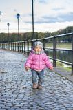 Little girl walks along the waterfront. In the autumn afternoon Royalty Free Stock Photography